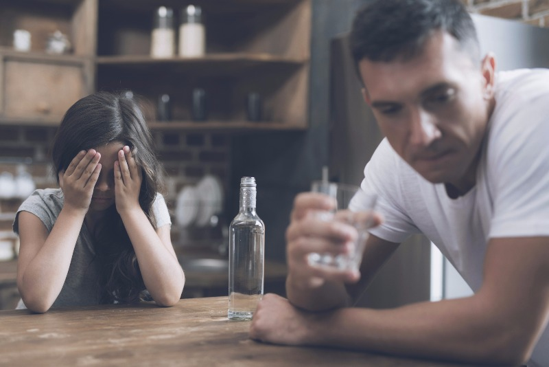 A little girl sits at a table and covers her face with her hands and cries while her father sits and drinks, turning away from her with shame.