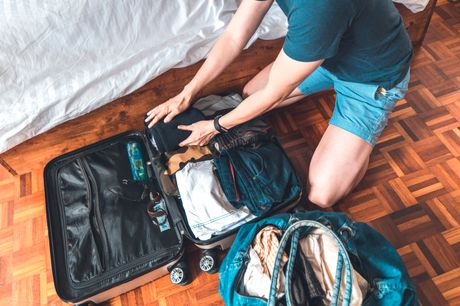Man packing suitcase and weekend bag with clothing.